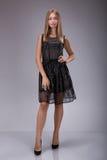 Full längdstående av en härlig blond kvinna i liten svart modeklänning royaltyfri bild