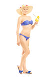 Full längdstående av en kvinna i bikinin som rymmer en coctail Arkivfoto