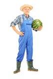 Full längdstående av en le bonde som rymmer en vattenmelon arkivfoto