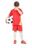Full längdstående av en ledsen pojke med fotbollbollen Arkivbild