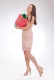 Full längdstående av en lycklig kär gåva för ung kvinna Arkivbild