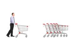 Full längdstående av en man som går en tom shoppingvagn tillbaka fotografering för bildbyråer
