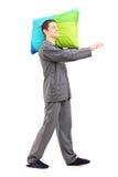 Full längdstående av en man som sleepwalking och rymmer en kudde Arkivfoton