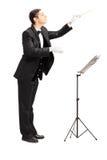 Full längdstående av en manlig orkesterledare som riktar intelligens Arkivfoton