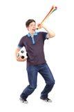 Full längdstående av en manlig sportfan som rymmer en fotboll och Royaltyfri Bild