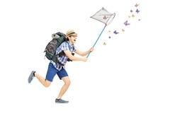 Full längdstående av en manlig turist som fångar fjärilar med Royaltyfri Bild