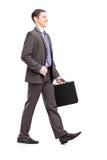 Full längdstående av en ung affärsman med portföljwalki Royaltyfri Bild