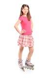 Full längdstående av en ung flicka på rullskridskor Arkivfoto