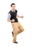 Full längdstående av en ung gladlynt man som gör en gest lycka Fotografering för Bildbyråer