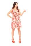 Full längdstående av en ung kvinna i en klänning som ger en tum royaltyfria foton