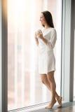 Full längdstående av en ung kvinna nära fönstret Arkivfoton