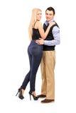 Full längdstående av en ung man och kvinna i en omfamning Arkivfoton