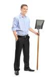 Full längdstående av en ung man som rymmer en skyffel Arkivbild