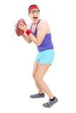 Full längdstående av en ung nerdy grabb som spelar fotboll Arkivbild
