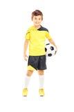 Full längdstående av en unge i sportswearen som rymmer en fotbollbal Arkivbilder