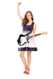 Full längdstående av en upphetsad kvinnlig som spelar på elektriska gu Arkivbilder