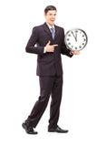 Full längdstående av en younman i dräkt som pekar på en klocka Fotografering för Bildbyråer