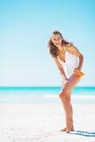 Full längdstående av kvinnan som applicerar kräm för solskärm royaltyfria bilder