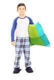 Full längdstående av pojken i pyjamas som rymmer en kudde Arkivfoto
