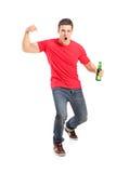 Full längdstående en upprymd fan som rymmer en ölflaska Arkivbild