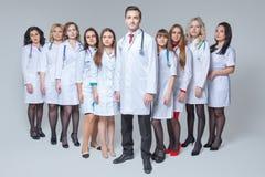 Full l?ngdst?ende av en attraktiv manlig doktor som blir p? huvudet av gruppen av doktorer fotografering för bildbyråer