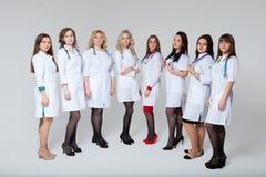 Full l?ngdst?ende av en lyckad grupp av doktorer som framme blir av gr? bakgrund royaltyfria foton