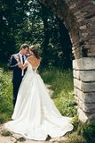 Full-lenght outdoor portrait of the happy attractive newlyweds softly hugging and rubbing noses under the stone arch in. The forest Royalty Free Stock Photos