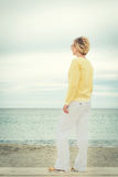 Full lenght portrait of young woman looking through the sea Royalty Free Stock Images