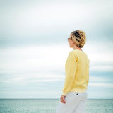 Full lenght portrait of young woman looking through the sea Stock Image