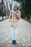 Full lenght vertical portrait of young woman wearing beige trench coat stock photography