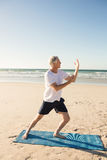 Full length of active senior man practicing yoga at beach. During sunny day Royalty Free Stock Photo
