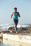 Full length African american woman running by the sea Stock Images