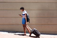 Full length african woman walking outdoors with suitcase and cell phone Royalty Free Stock Photography