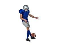 Full length American football player kicking ball Stock Images