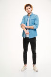Full length of angry young man rolling up his sleeves. Over white background Royalty Free Stock Images