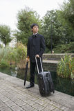 Full length of Asian businessman with luggage standing by pond Stock Photo