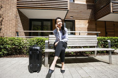 Full length of asian businesswoman answering cell phone while sitting by luggage on bench against building Stock Photography