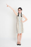 Full length Asian Chinese girl pointing on blank space Royalty Free Stock Photo