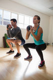 Full length of athletes exercising with kettlebells. In gym Royalty Free Stock Photo