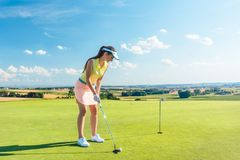 Full length of an attractive woman holding a golf club before hitting the ball stock image