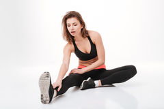 Full length attractive young woman athlete sitting and stretching legs. Over white background royalty free stock image