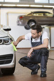 Full length of automobile mechanic cleaning car in workshop Royalty Free Stock Image