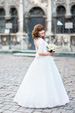 Full-length back photo of the bride in the long wedding dress holding the bouquet. Street location. Royalty Free Stock Images