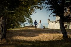 Full-length back view of the amazing newlywed couple holding hands and enjoying the landscape while walking near the old. Palace Royalty Free Stock Photos