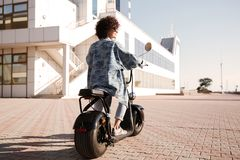 Full-length back view image of young girl rides on motorbike Royalty Free Stock Image
