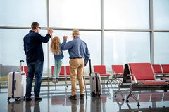 Cheerful family is waiting for flight. Full length back view of joyful adult father and grandfather are having fun with little girl. They are standing near big Royalty Free Stock Images