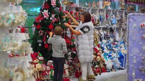The full-length back view of the joyful mother and son decorating the Christmas tree in the shopping center. stock video footage