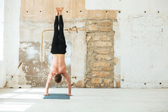 Full length back view of a man practising yoga poses. Indoors Royalty Free Stock Image