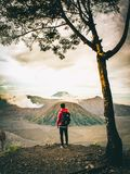 Full length of Backpacker Looking at Mountains while standing on field againts sky royalty free stock photos