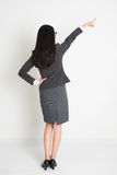 Full length backside Asian business woman pointing Royalty Free Stock Photo
